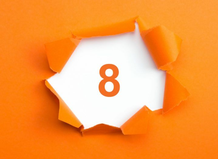 Illustration of the number eight on a white background inside an orange wall with paint tearing off.