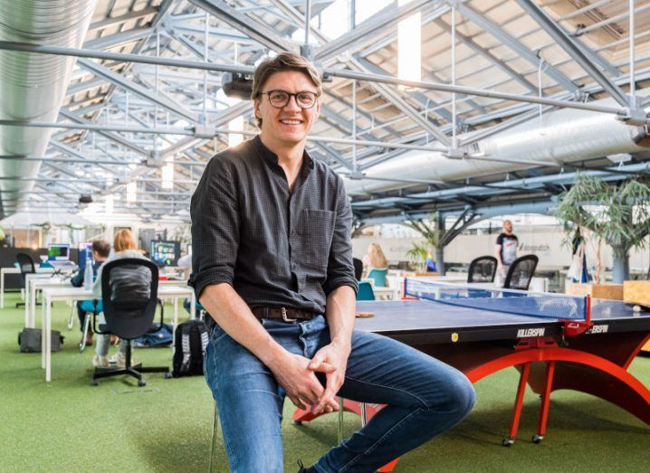 Patrick Walsh, dressed in a casual grey shirt and jeans, sits on a stool amid the Dogpatch Labs workspace which includes open plan desks and chairs and table tennis.