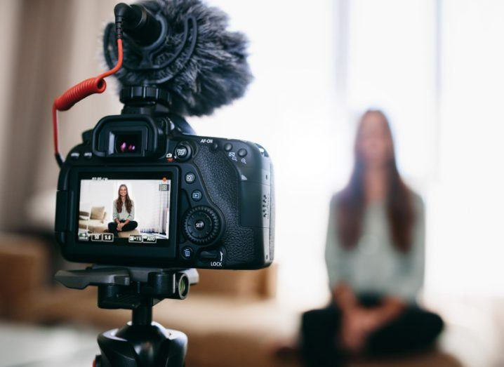 A stock image of a person talking into a video camera.