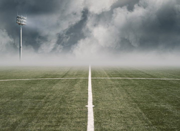 Empty football pitch shrouded in fog and clouds.