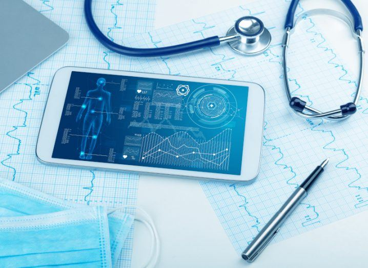 A stock image of a tablet displaying healthcare data beside a stethoscope, surgical masks, and ECG printouts.