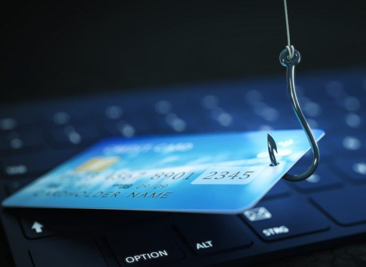 Laptop with a credit card resting on its keyboard. A fish hook is piercing the credit card to make it look like a phishing scam concept.