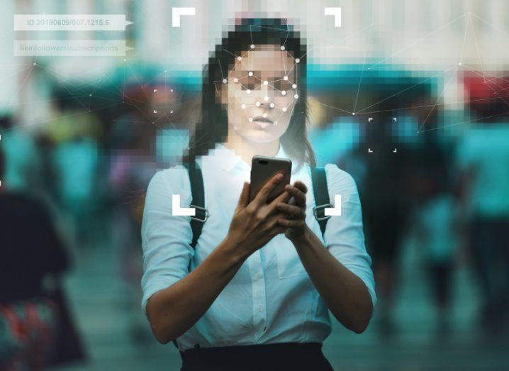 Girl in a school uniform with blurred out face holding a smartphone in a data protection themed image.