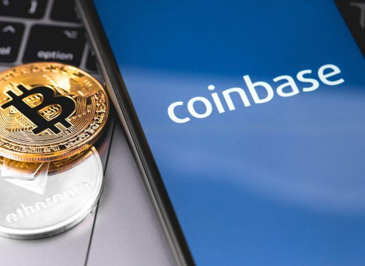 The Coinbase logo on a phone beside tokens representing Ethereum and Bitcoin.