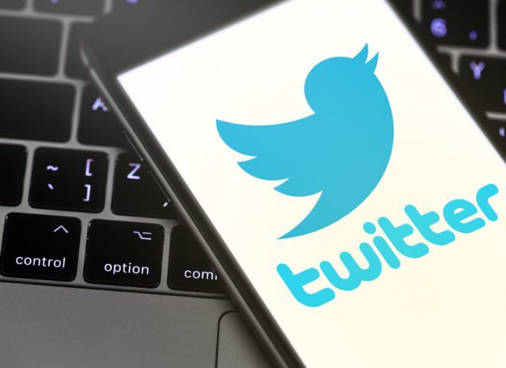 A phone displaying the Twitter logo is resting on a laptop keyboard.