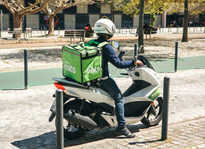 An Uber Eats gig worker on a moped setting out for a food delivery in Lisbon.