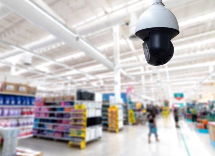 A stock image of a CCTV camera above a shop floor.