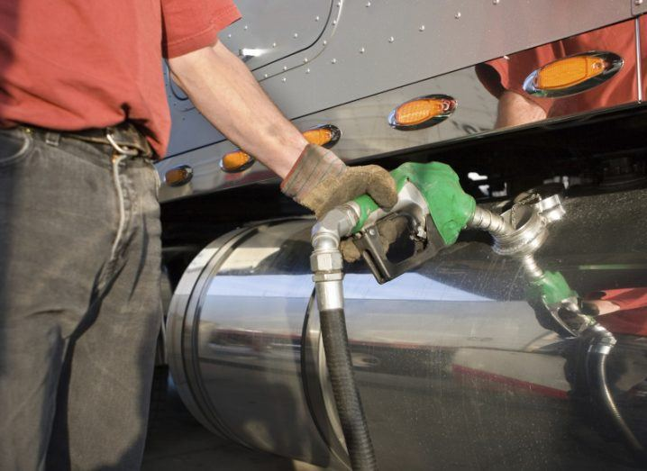A stock image of a man putting fuel into a truck.