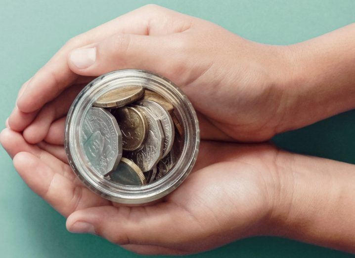 Pair of hands holding a jar of coins against a light blue background.