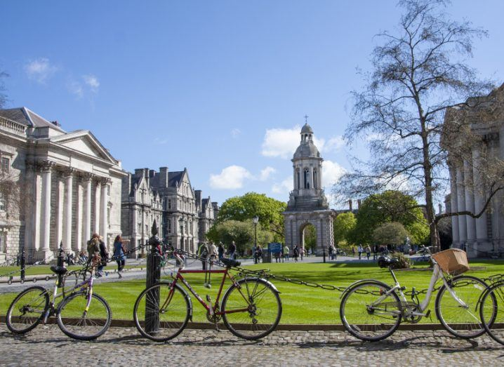 Bikes and students on the campus of Trinity College Dublin on a sunny day.