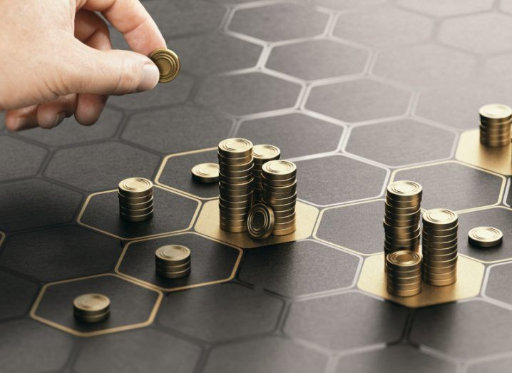 A graphic representing investment, showing stacks of coins on a number of tiles on a tiled surface.