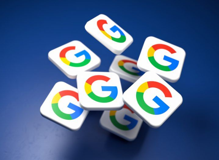 Square counters bearing a colourful G icon for Google scattered across a blue table.