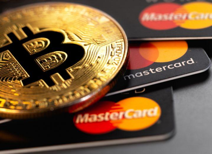 A number of Mastercard cards next to a physical representation of a Bitcoin.