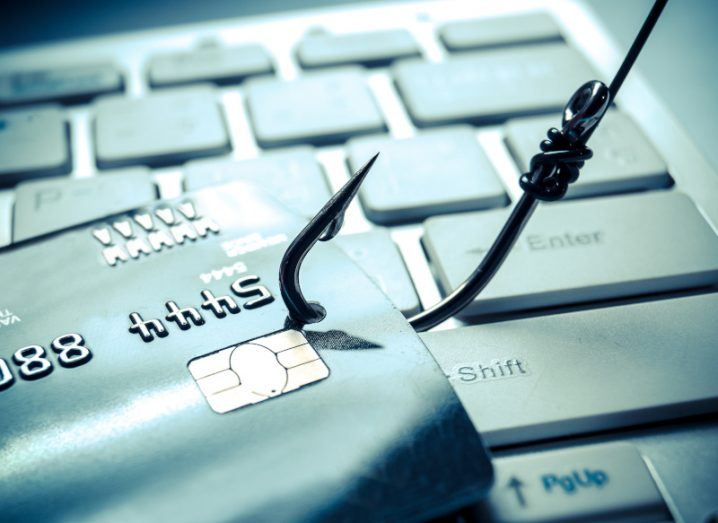 An image of a fishhook snagging a credit card on top of a computer keyboard, representing cybercrime.