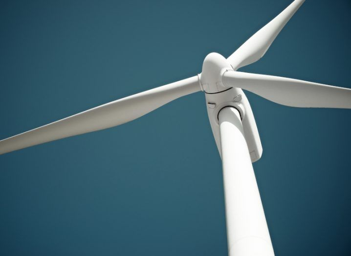 A stock image of a wind turbine against a blue sky.