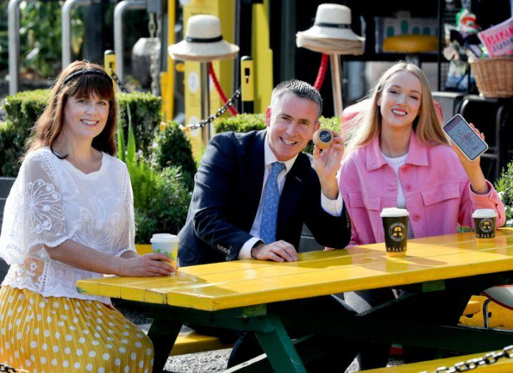 Jenny Melia, Damien English and Katie Farrell sitting outdoors at a picnic table at a cafe in Dublin.