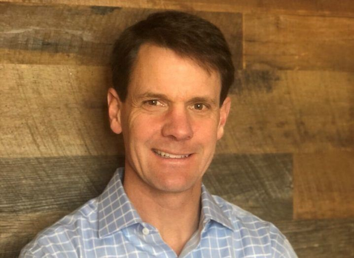 A close-up headshot of a man in a check shirt smiling at the camera against a wooden wall. He is the CIO of Workato.