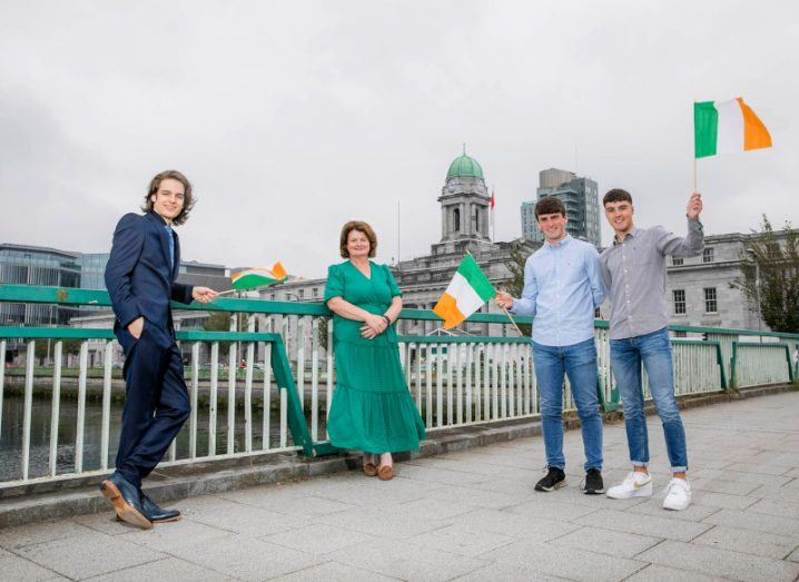 Three young men and an older woman stand on a bridge in Dublin's city centre. The young men are holding up small Irish flags and the woman is wearing an emerald green dress.