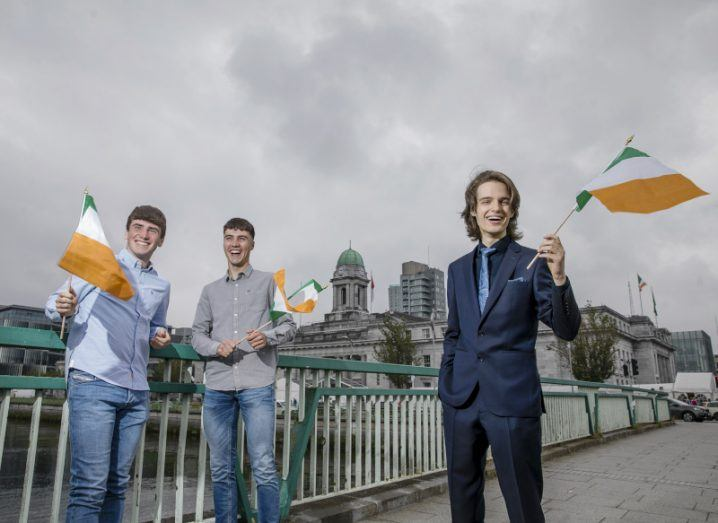 Three young men stand on a bridge in a city, each waving small Irish flags.