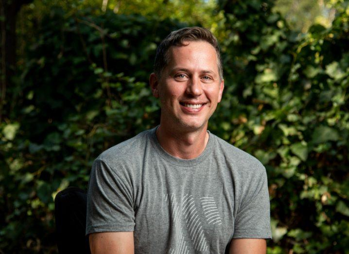 A man in a grey T-shirt smiles against a background of green foliage.