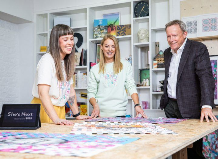 Gillian Henderson, Jill Deering of Jill&Gill with Visa's Dominic White standing in a studio looking at design templates laid out on a table.