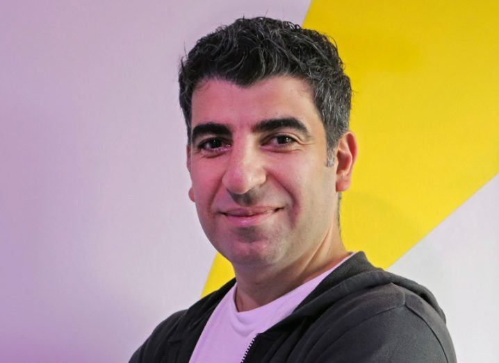 A man stands sideways but faces the camera. He's wearing a grey hoody and a white t-shirt. He stands against a pink and yellow wall.
