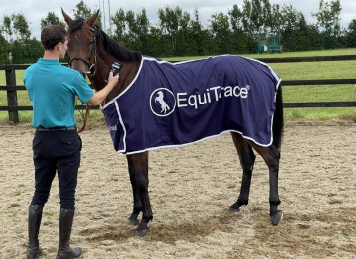 A man is standing in a field with a horse. The horse is wearing a cover that says EquiTrace, and the man is holding a tech device up to the animal.