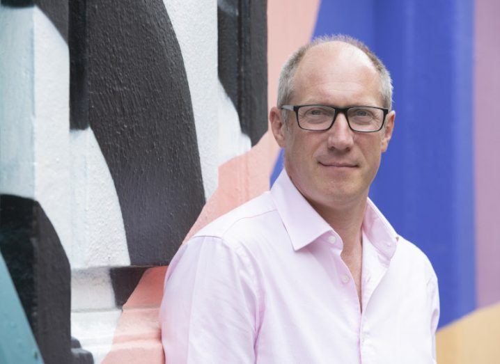 Spark Crowdfunding CEO Mark Burge is standing in front of a colourful wall.