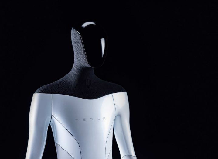 A concept image of the Tesla Bot, a glossy chrome robot with a humanlike figure, black mesh neck and shoulders, and shiny black visor.