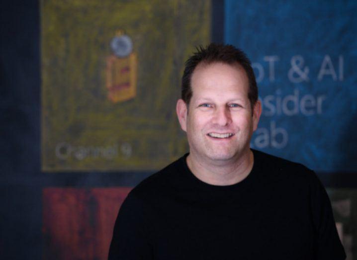 A headshot of a man in a black T-shirt.