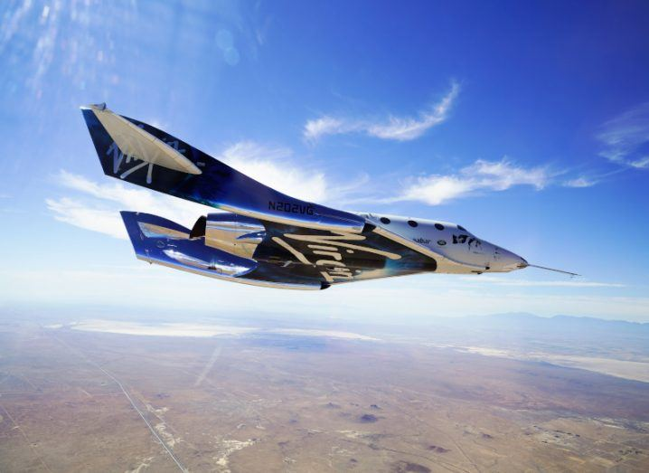 The VSS Unity is gliding back to Earth after its second supersonic flight. The sky is mostly clear with a few cirrus clouds and the ground is a dark brown colour with little vegetation or buildings.