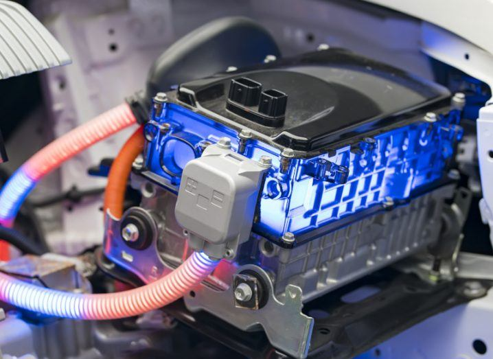 A battery used in electric vehicles is shown. There are two red tubes connected to the main body of the battery, which is black. The battery is also glowing blue.