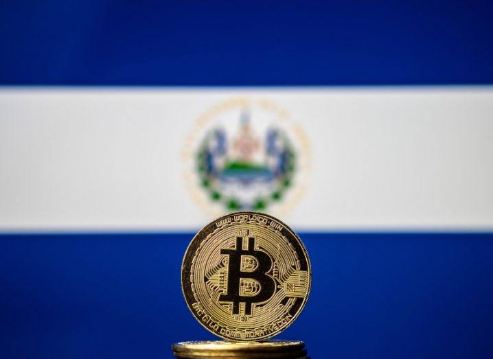 Image of a physical bitcoin in the backdrop of the El Salvador blue-and-white flag.
