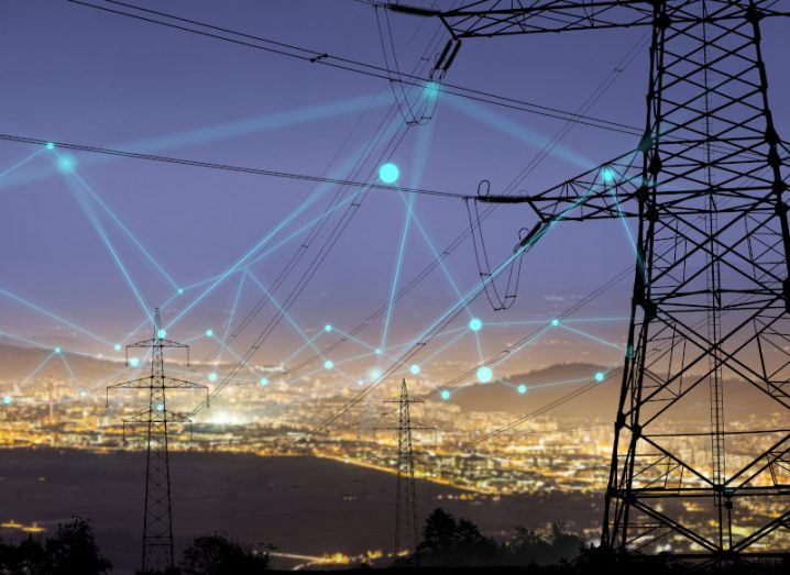 Image of electricity poles connected to each other with a city in the background.