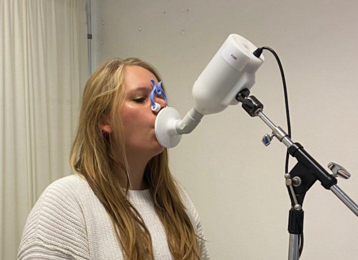 Nynke Wijbenga is standing in front of the electronic nose machine. She has a page over her own nose, closing the nostrils so all of the escaping exhaled air is captured by the device.