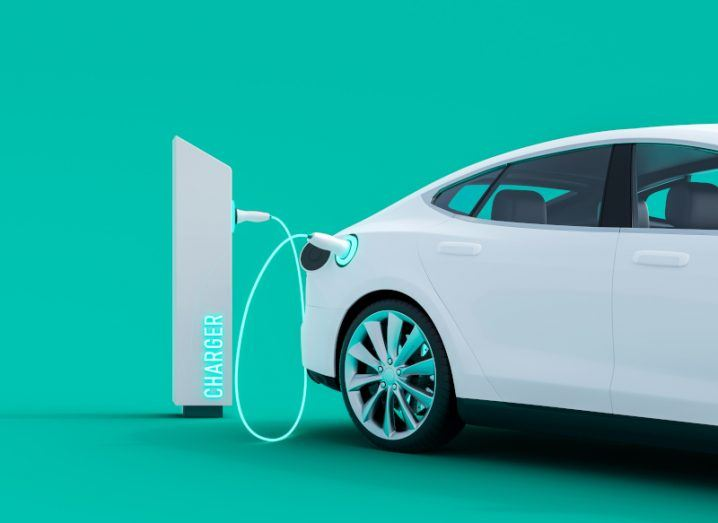 A white electric vehicle being charged at a charging point with a green background.