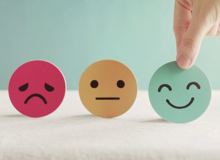 A hand choosing a green smiley face cut-out over an orange straight face and red sad face.