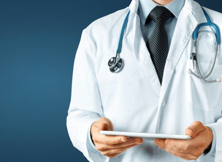 Doctor holding a tablet device in hand in front of a blue background.