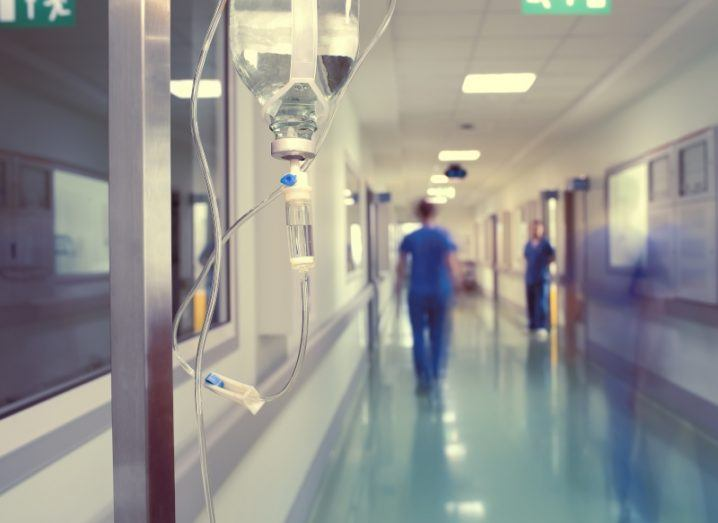 A hospital corridor is pictured where health projects are likely to be implemented. There is a drip directly in front of the camera and doctors and nurses can be seen in the background. It is a time lapse image and so the people are blurred to show that they are moving.