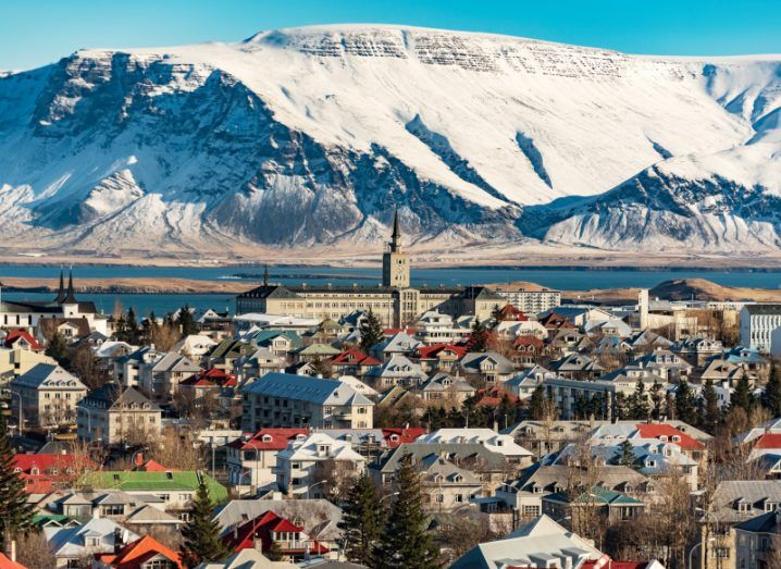 Reykjavik, Iceland, where Crowberry Capital is based, is pictured in the wintertime. Buildings are visible at the front of the photo, while there are snow-capped mountains and a lake at the background, beneath a clear blue sky.