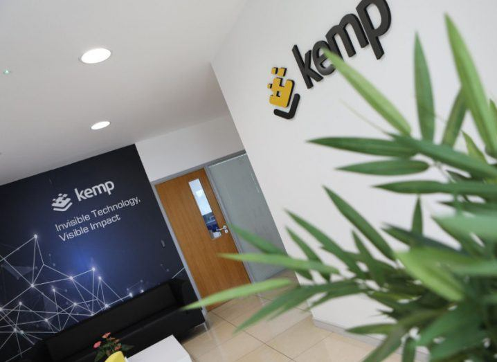 Inside Kemp Technologies' office where its logo is displayed on the wall alongside the words 'Invisible technology, visible impact'. The reception is decorated with potted plants.