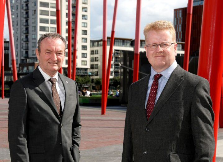 Tekenable managing director Nick Connors and CTO Peter Rose standing in Dublin's Grand Canal Dock with red sculptures behind them.