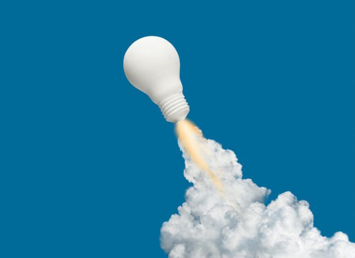 A lightbulb is positioned like a rocket blasting off, with flames and smoke coming from the bottom of it.