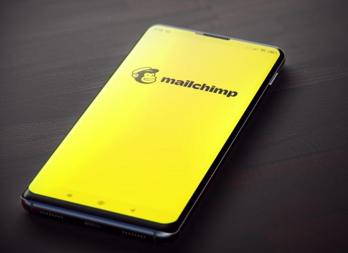 A phone with Mailchimp software is on the table. The yellow Mailchimp branding and the monkey logo are clearly visible on the phone screen.