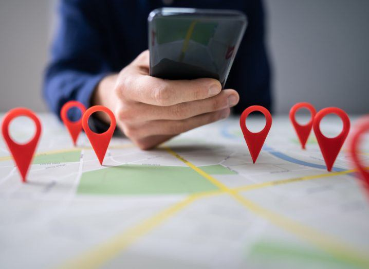 Stalkerware concept: A physical map laid out in front of a person holding a phone. The map has 3D red pins standing up on various locations on the map.
