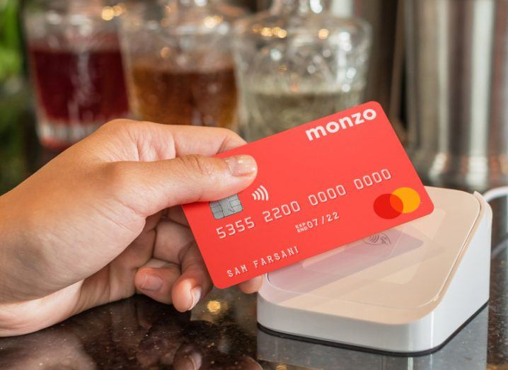 A hand holding a Monzo card and tapping it on a contactless payment machine.