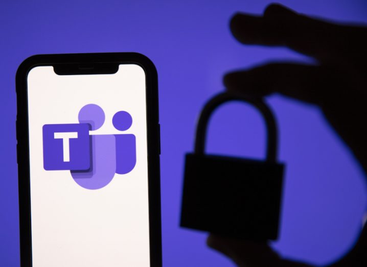 Microsoft Teams logo on a smartphone with a silhouette of a hand holding a lock against a purple background.