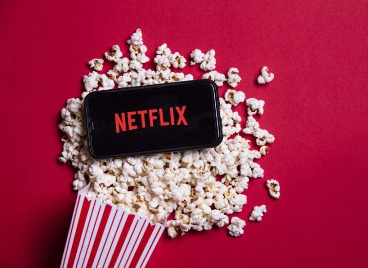 Netflix logo on smartphone placed above popcorn on a red background.
