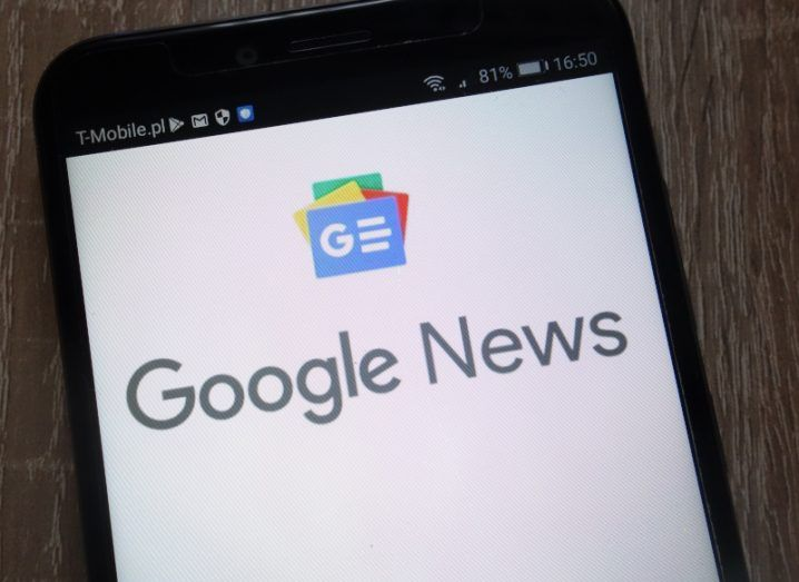 Smartphone on wooden table with Google News logo on the screen.