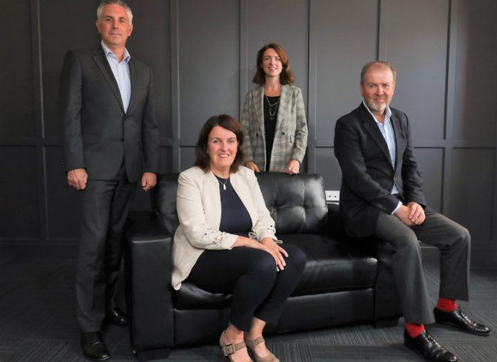 Photo of Andrew Jenkins, Karen Bradbury, Roisin Finnegan and Alex Lee. They're all wearing formal clothing, with some seated on a sofa and others standing around it.